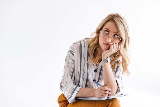 Blond poważna kobieta w okularach podpierających głowę i patrząca w górę, siedząca na krześle odizolowanym nad białą ścianą