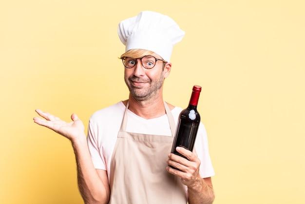 Blond przystojny szef kuchni dorosły mężczyzna trzymający butelkę wina