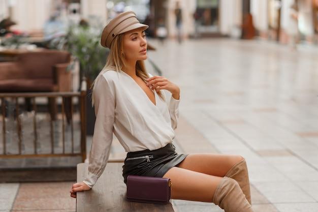 Blond sexy europejska kobieta w modnej czapce autun pozowanie na zewnątrz