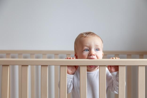 Blond słodkie niebieskookie małe dziecko w białym body, gryząc drewniane wezgłowie łóżka na białym wnętrzu