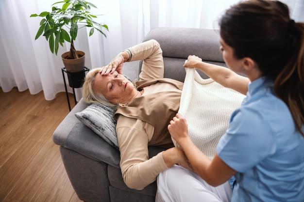 Blond starsza kobieta leżąc na kanapie i mając ból głowy, podczas gdy pielęgniarka zakrywa ją kocem.