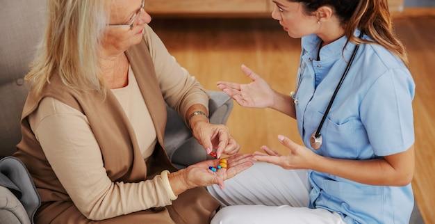 Blond starsza kobieta siedzi w domu i trzyma rękę pełną pigułek. pielęgniarka siedzi obok niej i udziela jej porad.