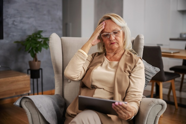 Blond starsza kobieta siedzi w domu, ma ból głowy i patrzy na tablet, aby uzyskać porady online.