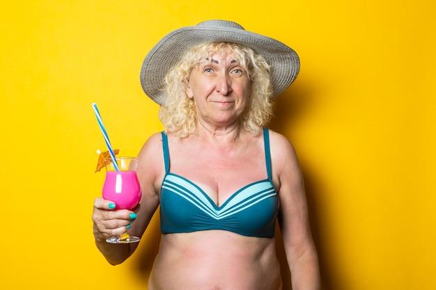 Blond staruszka w stroju kąpielowym trzyma koktajl na żółtej powierzchni