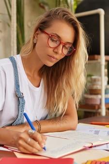 Blond studentka w optycznych okularach w czerwonych oprawkach zbiera materiały do pracy szkoleniowej