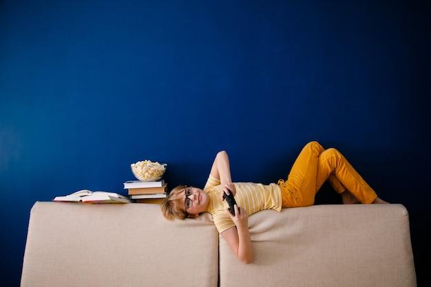 Blond uczeń gra w gry wideo, zamiast uczyć się lekcji, trzyma gamepad