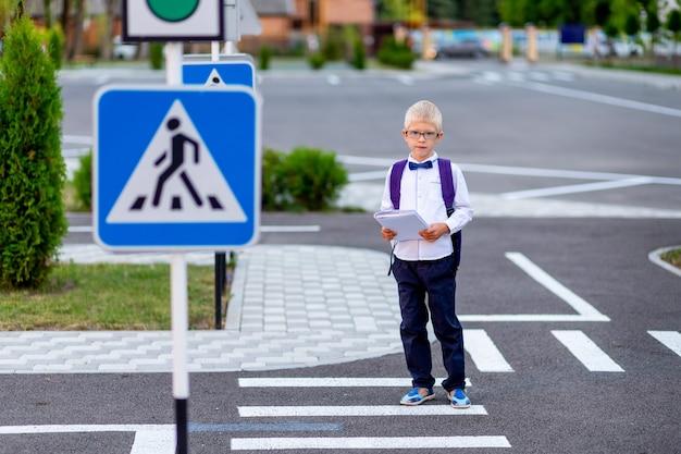Blond uczeń w okularach i plecaku idzie do szkoły na przejściu dla pieszych