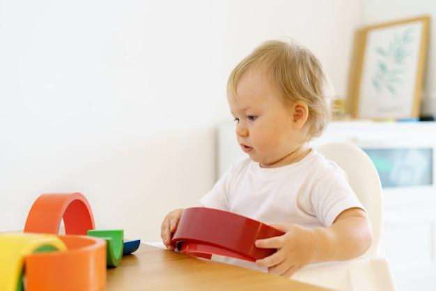 Blond urocza maluch bawi się zabawkami puzzlowymi koncepcja przestrzeni kopii rozwoju motorycznego dziecka