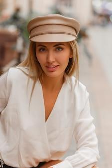 Blond uśmiechnięta europejska kobieta w modnej czapce autun pozowanie na świeżym powietrzu