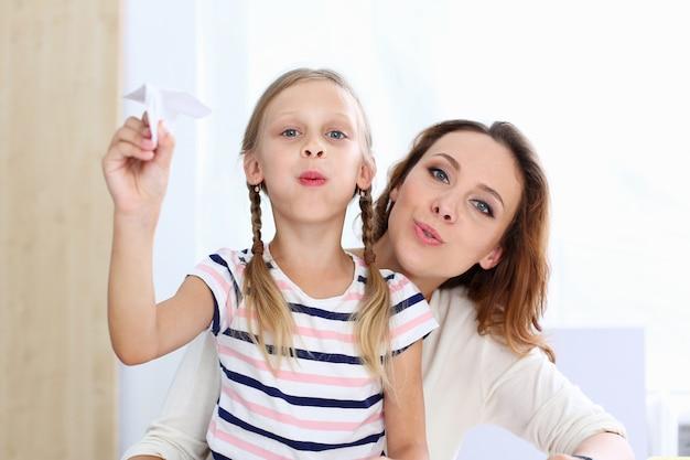 Blond uśmiechnięta mała dziewczynka robi papierowemu samolotowi