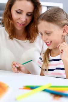 Blond uśmiechnięty mała dziewczynka chwyt w ręka ołówkowym rysunku