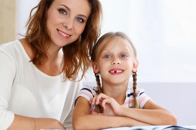 Blond uśmiechnięty mały czytanie wraz z mamą