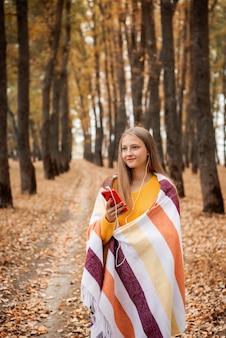 Blond wesoła dziewczyna stojąc na chodniku w parku jesienią i słuchając muzyki w słuchawkach. żółte liście na ziemi, uśmiechnięta osoba.