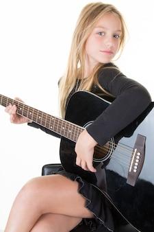 Blond wesoła młoda kobieta. piękno portreta nastolatka śliczna bawić się gitarę muzyka. młoda dziewczyna w bieli
