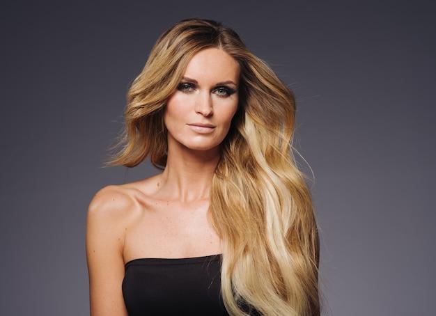 Blond włosy kobieta gładka blond fryzura dziewczyna model wieczorem styl. niebieskie tło.