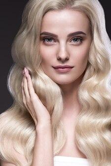 Blond włosy kobieta piękne kręcone fryzury faliste długie włosy naturalny makijaż. strzał studio. na czarno