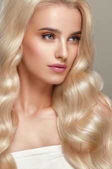 Blond włosy kobieta piękne kręcone fryzury faliste długie włosy naturalny makijaż. strzał studio. na szarym