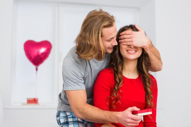 Blond włosy młody człowiek obejmujące oczy swojej dziewczyny, dając jej prezent