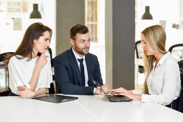 Blonde businesswoman wyjaśniające z laptopem do uśmiechu młodych cou