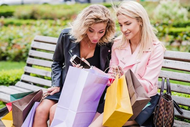 Blonde dziewcząt z torby na zakupy siedzi