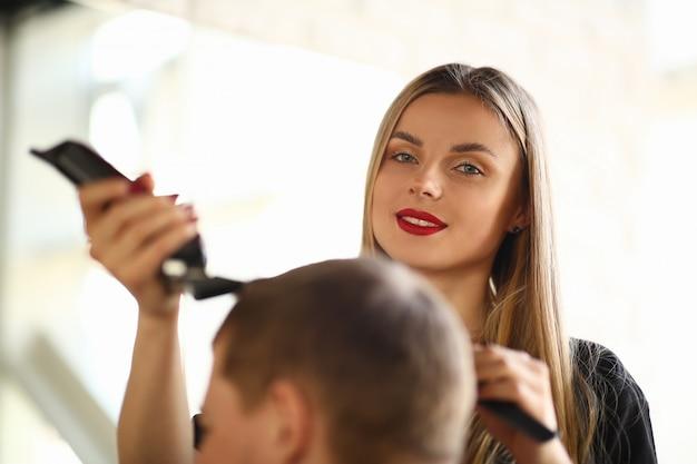 Blonde hairstylist cutting man by electric shaver. piękny fryzjer golenie męskich włosów marki razor. kobieca stylistka robi fryzurze dla klienta w zakładzie fryzjerskim.