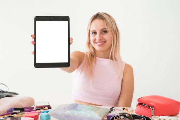 Blonde influencer pokazujący tablet