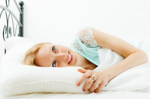 Blonde kobieta awaking w swoim łóżku w domu