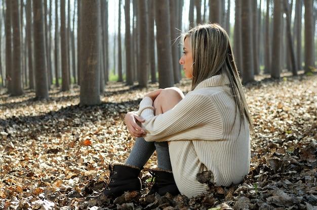 Blonde kobieta siedzi na liściach w lesie