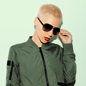 Blonde model w wojskowym stylu i modnych okularach przeciwsłonecznych