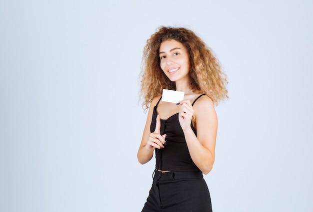 Blondie dziewczyna przedstawia lub odbiera wizytówkę z ufnością.