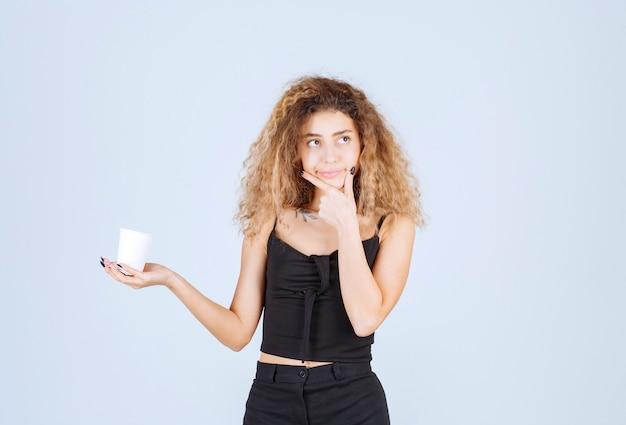 Blondie dziewczyna trzyma filiżankę kawy i myśli.