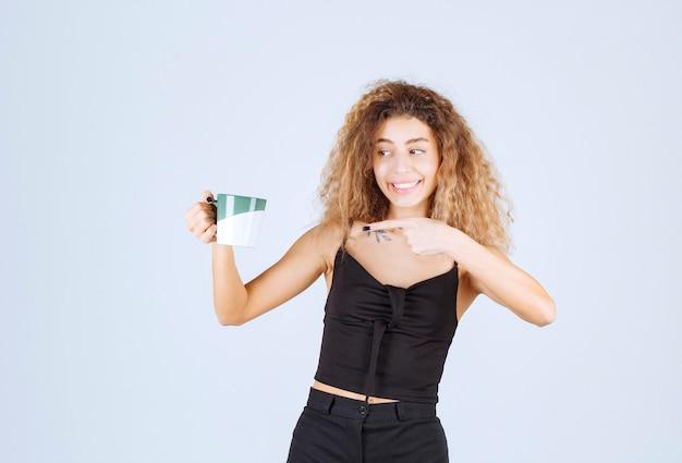 Blondie dziewczyna trzyma filiżankę kawy i wskazuje gdzieś.