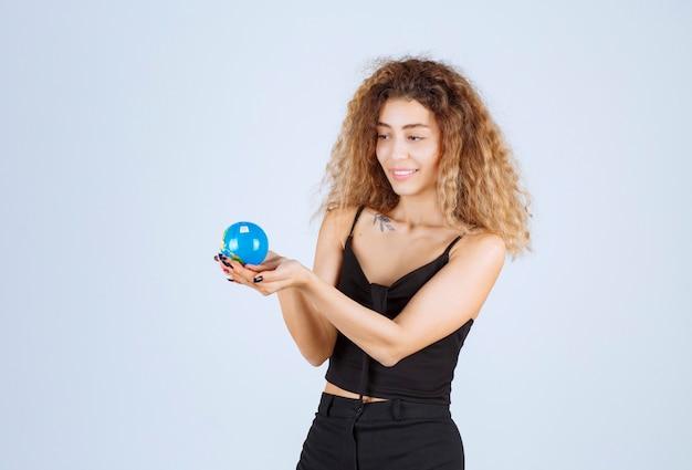Blondie dziewczyna trzyma mini kulę ziemską i czuje się pozytywnie.