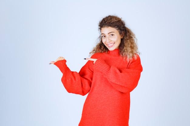 Blondie kobieta w czerwonej bluzie wskazująca gdzieś na lewą stronę.