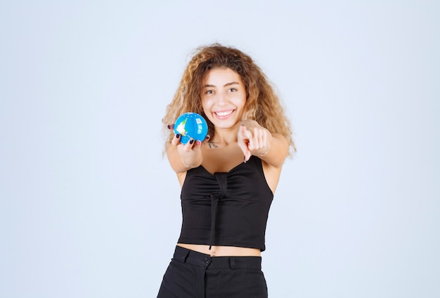 Blondie pokazuje swój mini globus swojemu partnerowi i zaprasza go do dzielenia się.