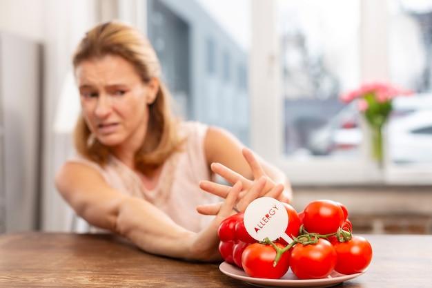 Blondwłosa kobieta z nadwrażliwością na alergeny nie je pomidorów