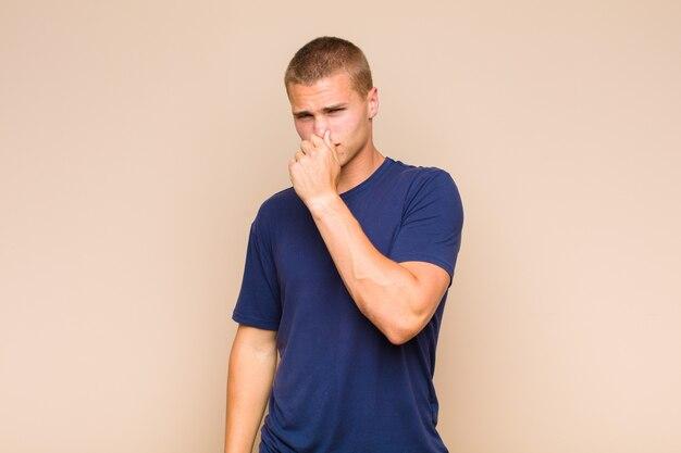 Blondyn czuje się zniesmaczony, trzyma nos, żeby nie poczuć nieprzyjemnego zapachu