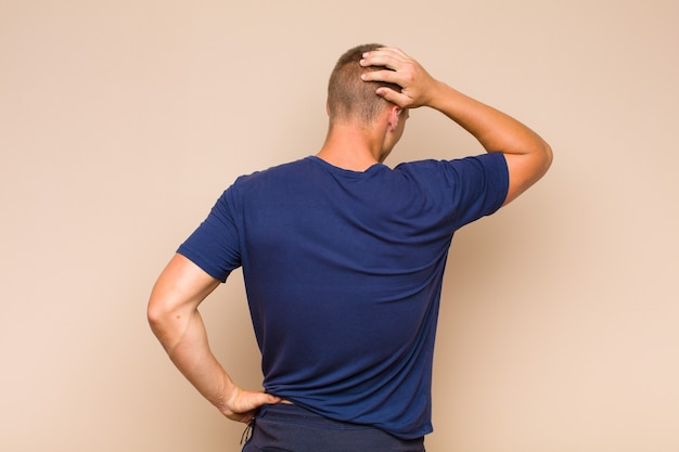 Blondyn myśli lub wątpi, drapie się po głowie, czuje się zdziwiony i zdezorientowany, widok z tyłu lub z tyłu