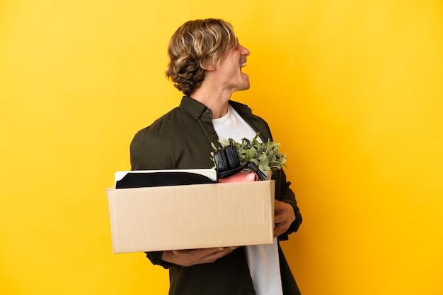 Blondyn robi ruch podnosząc pudełko pełne rzeczy na białym tle na żółtym tle, śmiejąc się w pozycji bocznej