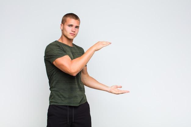Blondyn trzymający przedmiot obiema rękami na bocznej przestrzeni kopii, pokazując, oferując lub reklamując przedmiot