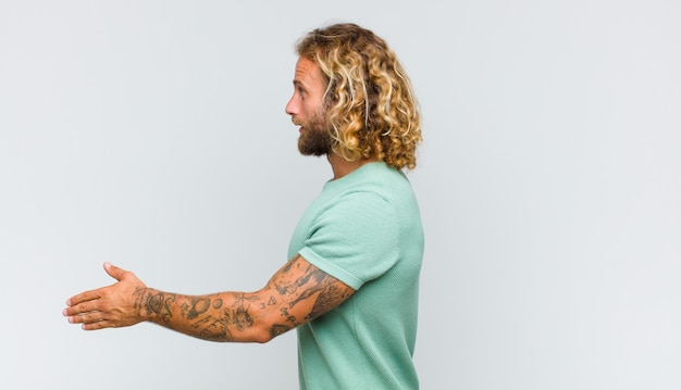 Blondyn uśmiecha się, wita i oferuje uścisk dłoni, aby zamknąć udaną transakcję, koncepcja współpracy