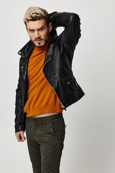 Blondyn w skórzanej kurtce, trzymając ręce za głową i pomarańczowe spodnie sweterkowe copy space.