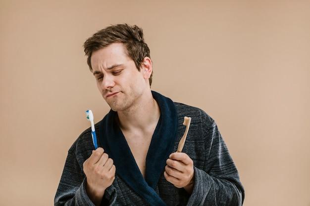Blondyn w szlafroku wybiera między drewnianą szczoteczką do zębów a plastikową
