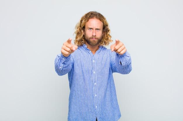 Blondyn wskazujący na aparat z obu palców i zły wyraz, mówiąc ci, abyś wypełnił swój obowiązek