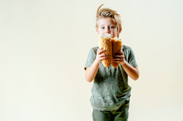 Blondyn zjada pachnącą bagietkę i świeże wypieki. smaczne śniadanie