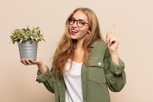 Blondyneczka czuje się jak wesoła i podekscytowana geniusz po zrealizowaniu pomysłu, radośnie podnosząca palec, eureka!