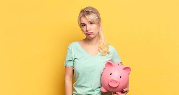 Blondyneczka czuje się smutna i jęczy z nieszczęśliwym spojrzeniem, płacze z negatywnym i sfrustrowanym nastawieniem