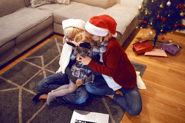 Blondynka babcia i młoda matka siedzą na podłodze w salonie i oboje przytulają śliczną dziewczynkę. kobiety o czapki mikołaja na głowie.