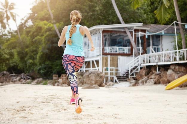 Blondynka biegacz w odzieży sportowej i trampkach robi ćwiczenia fizyczne na świeżym powietrzu na plaży podczas wakacji nad morzem.
