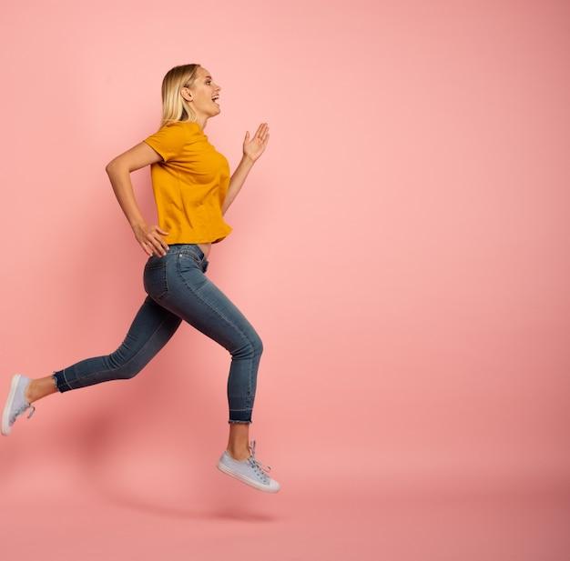 Blondynka biegnie szybko. pojęcie energii i witalności. różowe tło